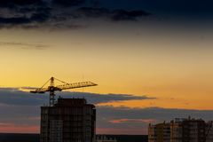 Construction tower crane,Industrial construction cranes on amazing sunset sky background. Crane,Construction tower crane equipment over building construction royalty free stock image