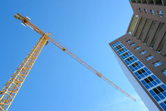 Construction tower crane and new building over blue sky background. Stock Photography