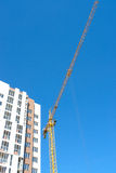 Construction tower crane and new building over blue sky background. Royalty Free Stock Photography