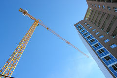 Construction tower crane and new building over blue sky background. Royalty Free Stock Image