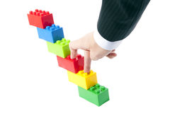 Construction toys, and a businessman's hand. Royalty Free Stock Images
