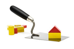 Construction trowel with house of toy blocks Royalty Free Stock Photos