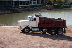 Construction truck. Sand gravel truck hauling load from lake Royalty Free Stock Images