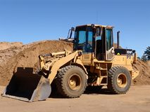 Construction Vehicle. Stationary Construction Vehicle in front of a heap of sand royalty free stock images