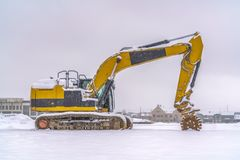 Construction vehicle on a winter landscape in Utah. Yellow construction vehicle that stands out against the snowy landscape in Daybreak, Utah. Metal wheels are stock image