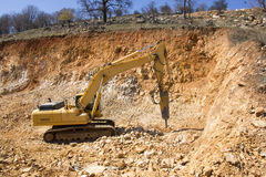 CONSTRUCTION VEHICLES. A large construction back hoe vehicle on a large rock pile with another construction vehicle working in the background. Sky is hazy to Stock Photos