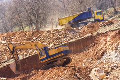 CONSTRUCTION VEHICLES. A large construction back hoe vehicle on a large rock pile with another construction vehicle working in the background. Sky is hazy to Royalty Free Stock Image