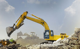 Construction vehicles. A large construction back hoe vehicle on a large rock pile with another construction vehicle working in the background.  Sky is hazy to