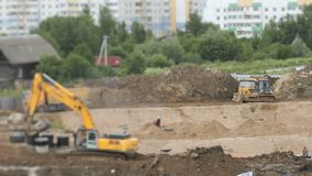 Construction vehicles and builders outdoors. Construction vehicles and builders on construction site in a summer season stock video footage