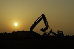 Construction vehicles in the sunset. You see the black silhouette of construction vehicles in the sunset Stock Photo