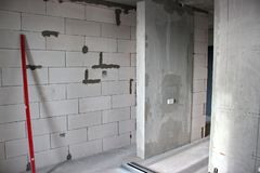 The construction of walls in the apartment with a free layout. the construction of walls of silicate blocks with carpenter`s leve. Construction of walls in the royalty free stock photo