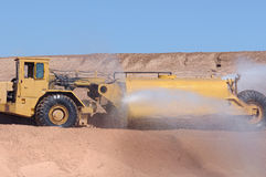 Construction water truck. A view of a yellow construction water tanker truck spraying water for dust control at construction site Stock Photo