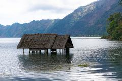 A construction that has been covered by the water, in the giant, in the giant crater of Danau Batur royalty free stock photography