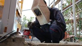 Construction Welder. Welder with protective equipment welding outdoors. Selective focus Stock Photography
