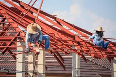 Welder workers installing steel frame structure of the house Stock Images