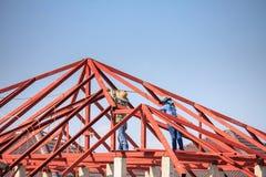 Welder workers installing steel frame structure of the house. Construction welder workers installing steel frame structure of the house roof at building stock photos