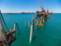 Construction of a wharf showing raked piles ready for headstock placement. The construction of a wharf in full flow with raked piles in place ready for stock photo