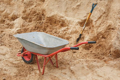 Construction wheelbarrow filled with sand a shovel Royalty Free Stock Images