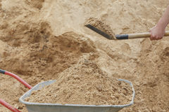 Construction wheelbarrow filled with sand a shovel Royalty Free Stock Image