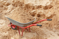 Construction wheelbarrow filled with sand a shovel Stock Image