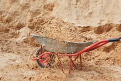 Construction wheelbarrow filled with sand a shovel Stock Photography