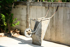 Construction wheelbarrow leaning against the wall. Royalty Free Stock Image