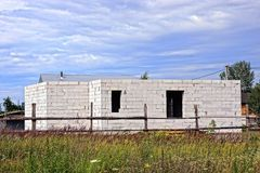 Construction of a white brick house outside a fence near a grass field. Frame of a building under construction from a white brick behind a wooden fence in the Royalty Free Stock Images