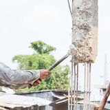Construction woker hitting movement remove concrete ploe with hammer Stock Photos
