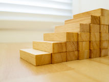 Construction of wood block stacking as step stair on wood floor. Concept of growth success business.  Stock Photos