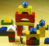 Construction wood game. Colorfull wooden pieces construction game with two litle ancient man figures stock images
