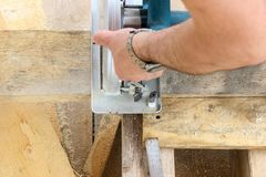 Construction of a wooden frame house - cutting a circular saw with boards stock photos