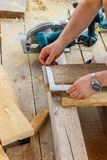 Construction of a wooden frame house - measuring the right size of the board, cutting off the saw blade with a saw, close up. stock images