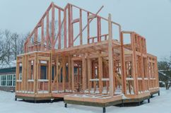 Construction of a timber frame house on piles. Construction of wooden frame house in winter royalty free stock photos