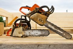 When construction a wooden house, two chainsaws a bit stock images