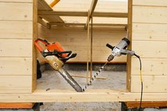 When construction a wooden house, two chainsaws a bit royalty free stock photo