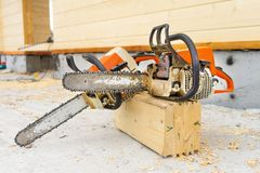 When construction a wooden house, two chainsaws a bit stock photo