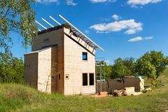 Construction of a wooden roof in an ecological house. External work on the building envelope. The wooden structure of the house ne Stock Images