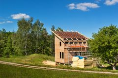 Construction of a wooden roof in an ecological house. External work on the building envelope. The wooden structure of the house ne Royalty Free Stock Photo