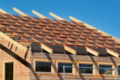 Construction of a wooden roof in an ecological house. External work on the building envelope. The wooden structure of the house ne Stock Photo