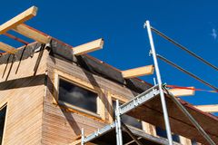 Construction of a wooden roof in an ecological house. External work on the building envelope. The wooden structure of the house ne Royalty Free Stock Images