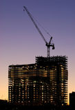 Construction Work 24/7. Building frame lit by reflectors at dusk royalty free stock photography