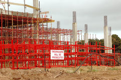 Construction work. A building site with a big red and grey big scaffolding with yellow warning sign TRESPASSERS WILL BE PROSECUTED outdoors Royalty Free Stock Photography