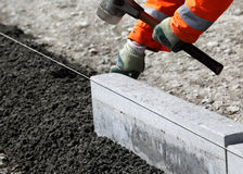 Construction work. A closeup view of a construction worker laying or placing a granite block at a construction site Stock Images
