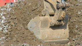 Construction work 3 8. A backhoe digs up gravel. The is a clip from a series about construction work stock video footage