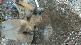 Construction work 6 8. A backhoe scoops out gravel. The is a clip from a series about construction work stock video