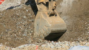 Construction work 5 8. A backhoe scoops up gravel. The is a clip from a series about construction work stock footage