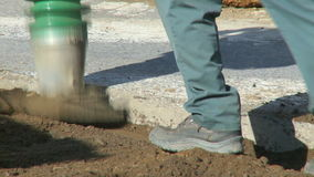 Construction work 1 8. The is a clip from a series about construction work.  A man walks behind a dirt compacter. heavy equipment can be heard backing up stock video footage