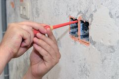 Construction work, the electrician installs the socket. Image of construction work, the electrician installs the socket royalty free stock images