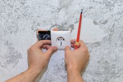 Construction work, the electrician installs the socket. Image of construction work, the electrician installs the socket stock images