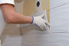 Construction work laying tile on the wall Royalty Free Stock Images
